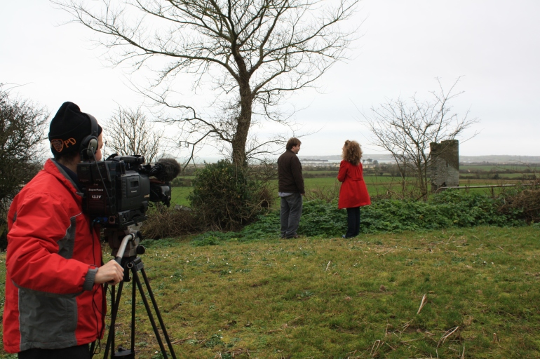 Karina Charles of Country Focus and Damian Shiels of Know Thy Place discuss Garryvoe Tower House (background)